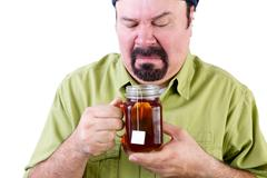 Uncertain middle aged man with healthy cup of tea Stock Photos