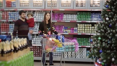 Beautiful family walking down the hall with a supermarket shopping carts and opt Stock Footage