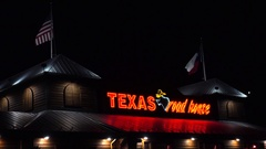 4K Texas Roadhouse BBQ steak restaurant, rooftop flags Stock Footage