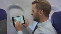 Corporate Businessperson Checking Pie Chart on Digital Tablet in Airplane Travel Stock Footage