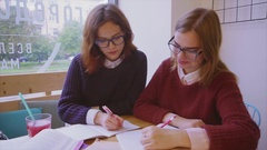 Female college students studies in the cafe two girls friends learning together Stock Footage