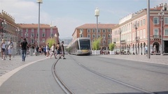 Tramway railway and people walk and drive bicycles at central Nice square France Stock Footage
