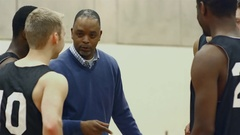 A basketball coach talking to his players in a huddle before a game Stock Footage