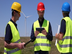 Engineers Men Holding Wind Turbine Plans and Speaking About Alternative Energy Stock Footage