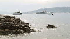 Waves splashing at rock stone at seashore coast with luxurious yachts in sea bay Stock Footage