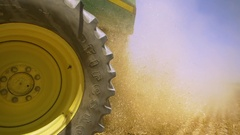 Slow motion of the rear wheel of a combine  with the hay sparkling on the sun Stock Footage