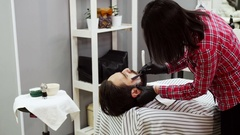 Barber shaves a white man with a straight razor Stock Footage