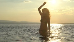 Sea life, waves and water splashes from a girl on the sunset background. Stock Footage