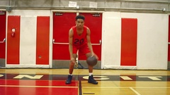 Basketball player dribbling the ball through his legs, toward the camera Stock Footage