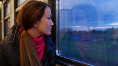 Woman look out from suburban train window with light smile, evening trip Stock Footage