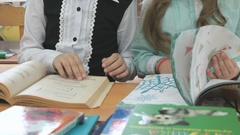 Little girls sitting at desk flips pages of book Stock Footage