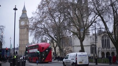 London in the fog: traffic at Big Ben and red bus Stock Footage