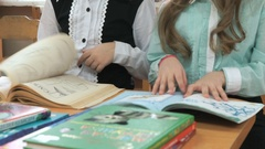 Preschoolers sitting at desk flips pages of book Stock Footage