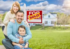 Mixed Race Family In Front of House and Sold For Sale Real Estate Sign Stock Photos