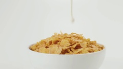 Milk pours in slow motion on a bowl of corn flakes Stock Footage