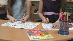 Children draw images in notebooks using pencils Stock Footage