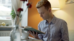 Man in a checked shirt sitting in the cafe and reading interesting book Stock Footage