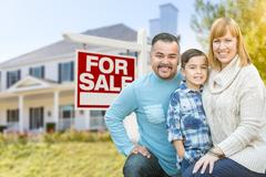 Mixed Race Family Portrait In Front of House and For Sale Real Estate Sign Stock Photos