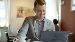 Handsome man in a tweed jacket watching something funny on laptop Stock Footage