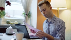 Man having problems with documents while checking outcomes on laptop Stock Footage