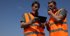 Airport Crew Men Work Digital Tablet and Walkie Talkie Aircraft Passing Overhead Stock Footage