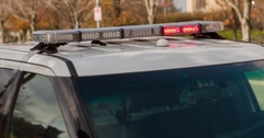 Police vehicle with lights flashing on side of street 4k Stock Footage