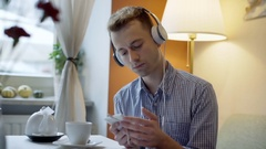 Absorbed man waiting for someone in the cafe while listening music on headphones Stock Footage