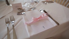 Festive table decoration arranged close up - menu napkin tied with pink ribbon Stock Footage
