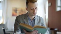 Man receives message on smartphone while reading book in the cafe Stock Footage