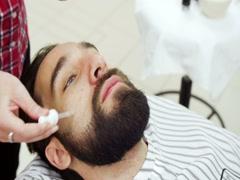 Hairdresser gets oil on beard Stock Footage