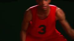 A basketball player dribbles the ball low to the ground Stock Footage