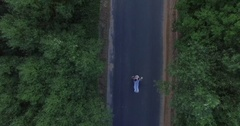 4K Man and woman crazy walking along the road in summer forest aerial top view Stock Footage