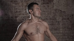 Muscular and fit mature bodybuilder posing demonstrates the core muscles Stock Footage