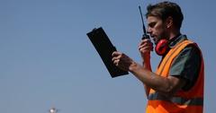 Airline Coordinator Man Talk Walkie Talkie Hold Clipboard Airplane Pass Overhead Stock Footage