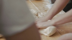 Women kneading rye dough for bread on table Stock Footage