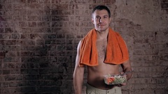 Fitness bodybuilder man holding a plastic bowl and eating fresh salad, on brick Stock Footage