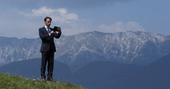 Confident Business Man Browsing Digital Tablet Check Data in a Nature Landscape Stock Footage