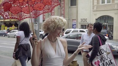Marilyn Monroe impersonator umbrella waving at tourists Hollywood Boulevard LA Stock Footage