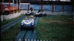 Children in minature cars, pony carts at amusemnet park, 3848 vintage home movie Stock Footage