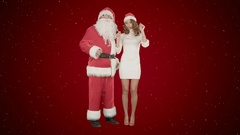 Beautiful happy woman dancing with Santa Claus on red background with snow Stock Footage