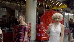 Marilyn Monroe impersonator red umbrella blowing kiss posing Hollywood Blvd LA Stock Footage