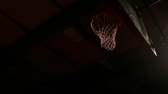 A basketball player dunks the ball, dark lighting, view from below Stock Footage