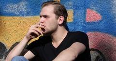 Sad Young Man Sitting Smoking Cigarette Tobacco Drug Addicted Graffiti Art Wall Stock Footage