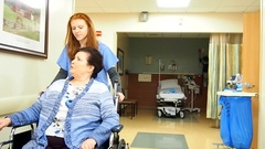 Pushing patient in wheelchair Stock Footage
