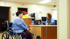 Nurse and patient at nurses station Stock Footage