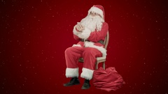 Santa laughing out loud as he talks on his cell phone on red background with Stock Footage
