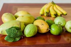 Fruits on the wooden table. Mangoes, bananas, tangerines, guava Stock Photos