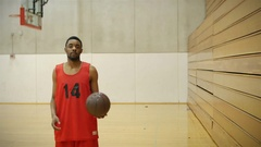 Portrait of a basketball player dribbling and spinning a ball by bleachers Stock Footage