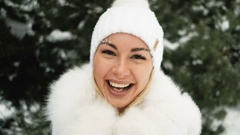 Happy woman in a white hat and furry mittens in green pines Stock Footage