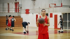 A basketball player on a court tossing a ball between his hands Stock Footage